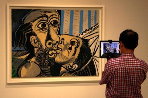 """A visitor uses his iPad to take a photograph of a painting titled """"The Kiss"""" at an exhibition showcasing works by Spanish artist Pablo Picasso in the Art Gallery of South Australia in Sydney"""