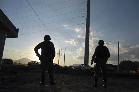 Soldiers guard a crime scene in the municipality of Cienega de Flores