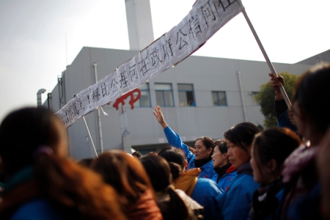 Workers on strike blocking the entrance gate of Hi-P International factory yell slogans during a protest in Shanghai