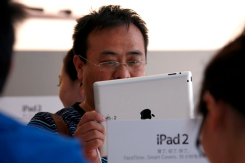 A customer looks at an iPad 2 during the China launch at an Apple Store in central Beijing