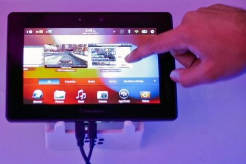 A conference attendee examines the BlackBerry PlayBook during its launch in Mumbai