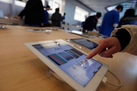 A customer tests out an Apple iPad at an Apple Store in downtown Shanghai