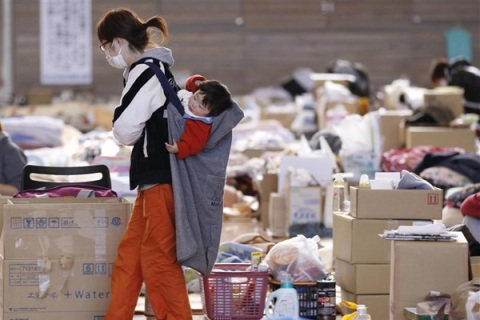 A woman carries her baby on her back at an evacuation centre in Fukushima, northern Japan