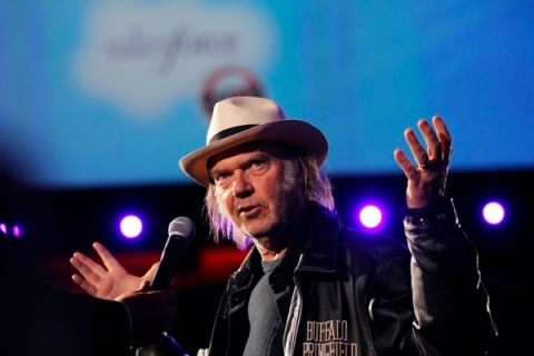 Canadian music legend Neil Young gestures as he address attendees at the Dreamforce event in San Francisco