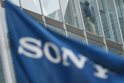 A worker cleaning inside Sony Corp's headquarters is pictured past a flag bearing the company's logo in Tokyo