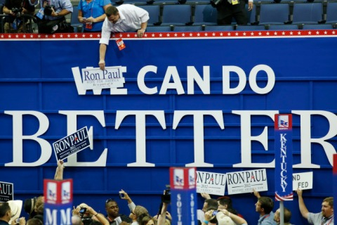 A Ron Paul for president supporter places a poster over a sign so that it reads Ron Paul Can Do Better during the opening session of the Republican National Convention in Tampa