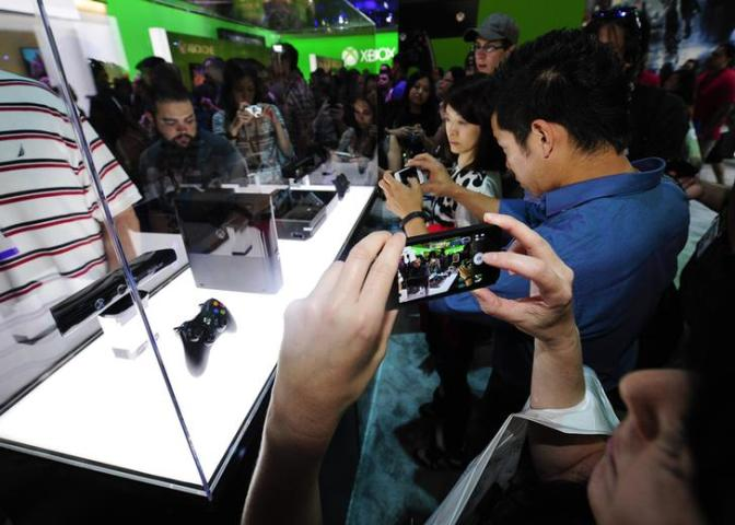 Gamers and journalists photograph the new Xbox One during E3 in Los Angeles, California
