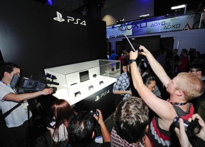Gamers and industry journalists photograph the new Play Station 4 on display at E3 in Los Angeles, California