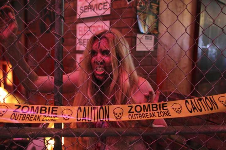A woman acts the part of a zombie at the Konami exhibit for the game Dead Rising 3 on the first day of E3, the Electronic Entertainment Expo, in Los Angeles, California.