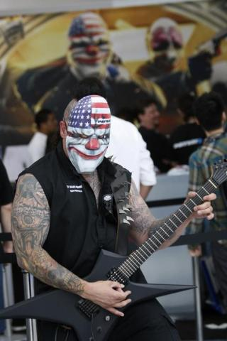 """Exhibitor for game """"Payday 2"""" plays guitar at E3, the Electronic Entertainment Expo, in Los Angeles"""