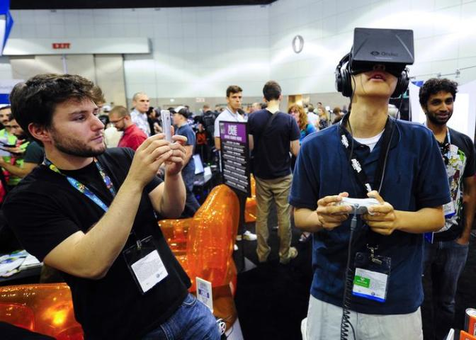Rectal software designer Julian Kantor takes a picture of Jonathan Feng as he uses the Oculus Rift virtual reality headset to experience his program during E3 in Los Angeles