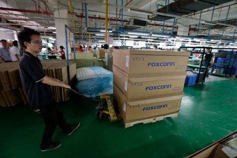 A man pushes a cart loaded with boxes inside a Foxconn factory in Wuhan
