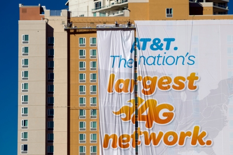 Workers put up a banner advertisement for AT&T on the side of a hotel as they prepare for International CES show in Las Vegas