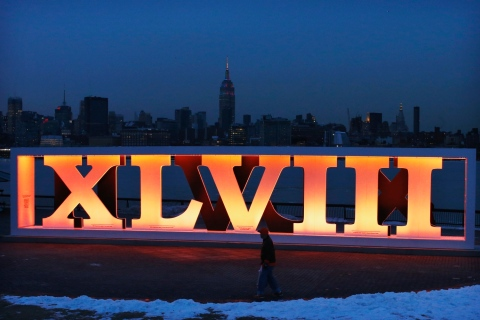 New York skyline and Empire State Building are seen in distance as man walks past roman numerals for NFL Super Bowl XLVIII football game in Hoboken