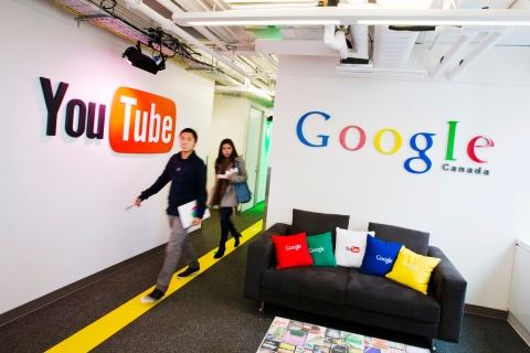 People walk by a YouTube sign at the new Google office in Toronto